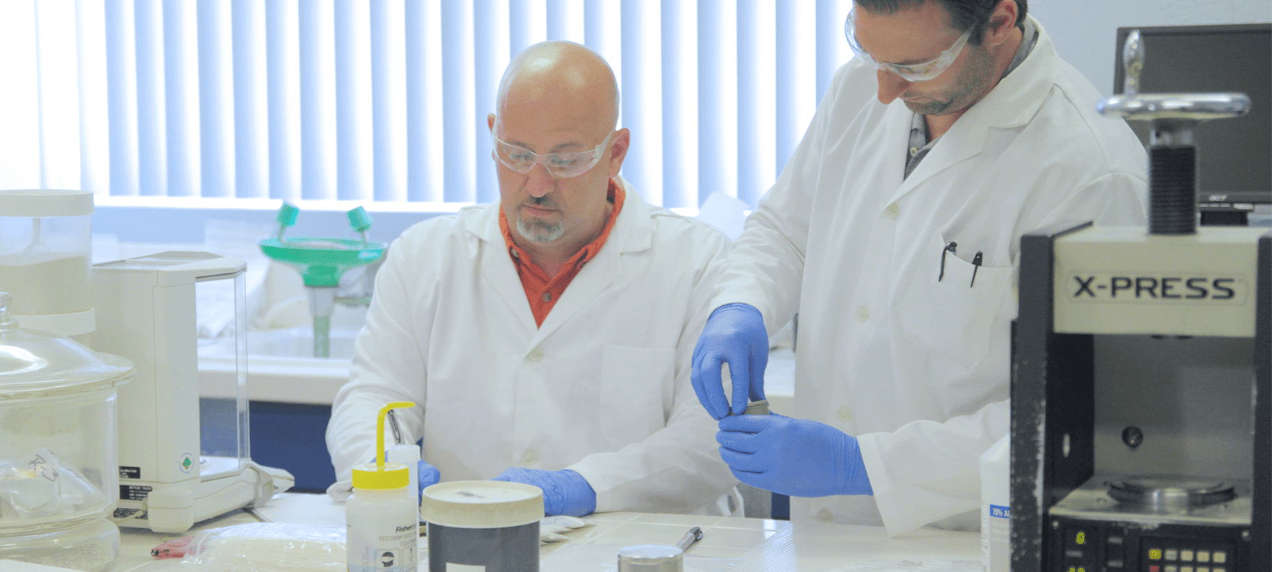 Two lab techs working on analysing samples